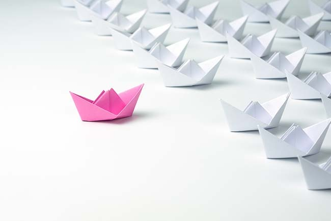 paper boats with pink in the lead